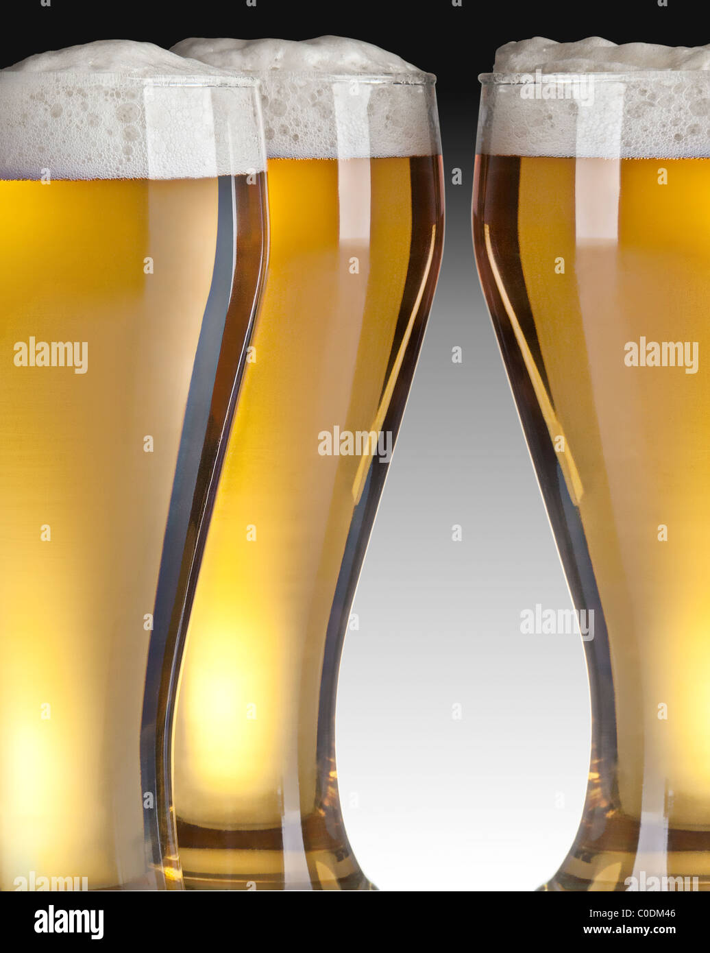 three glasses of beer on gray background - Stock Image