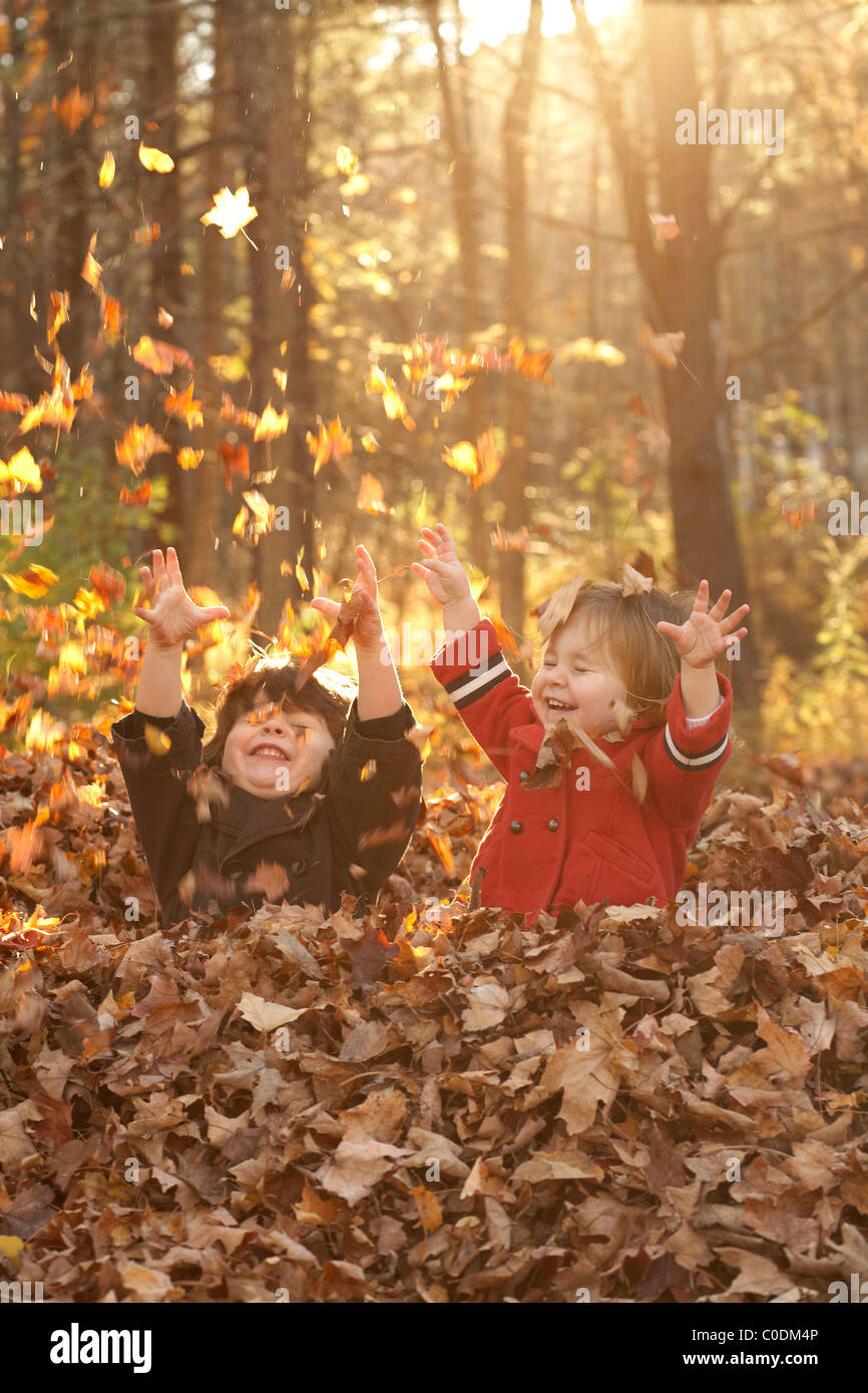 Little kids playing in fall leaves - Stock Image