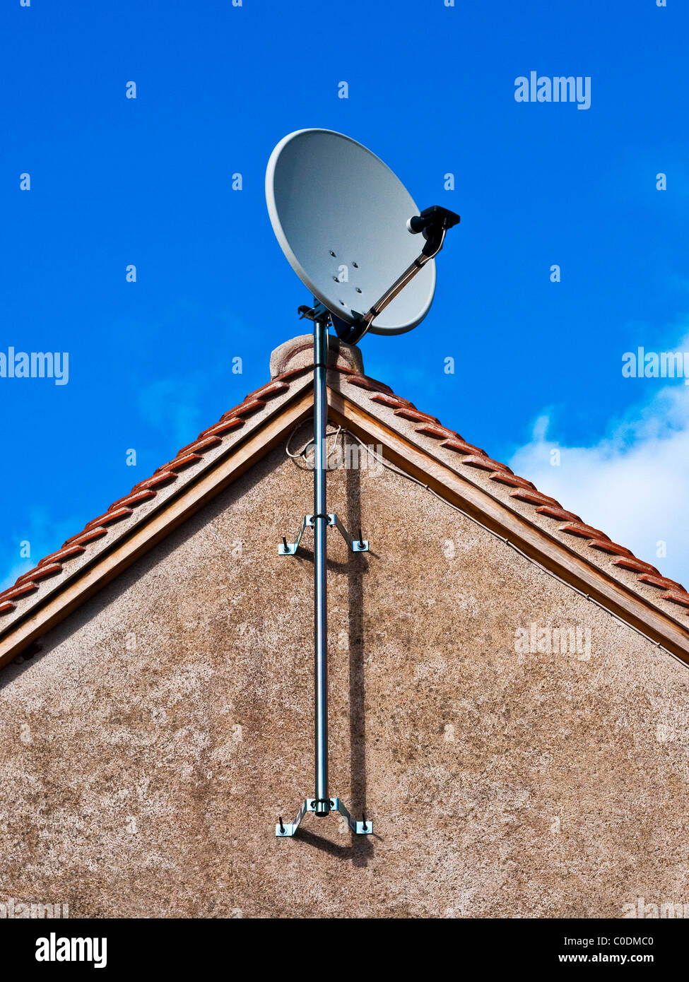Television dish on house end gable wall - France. - Stock Image