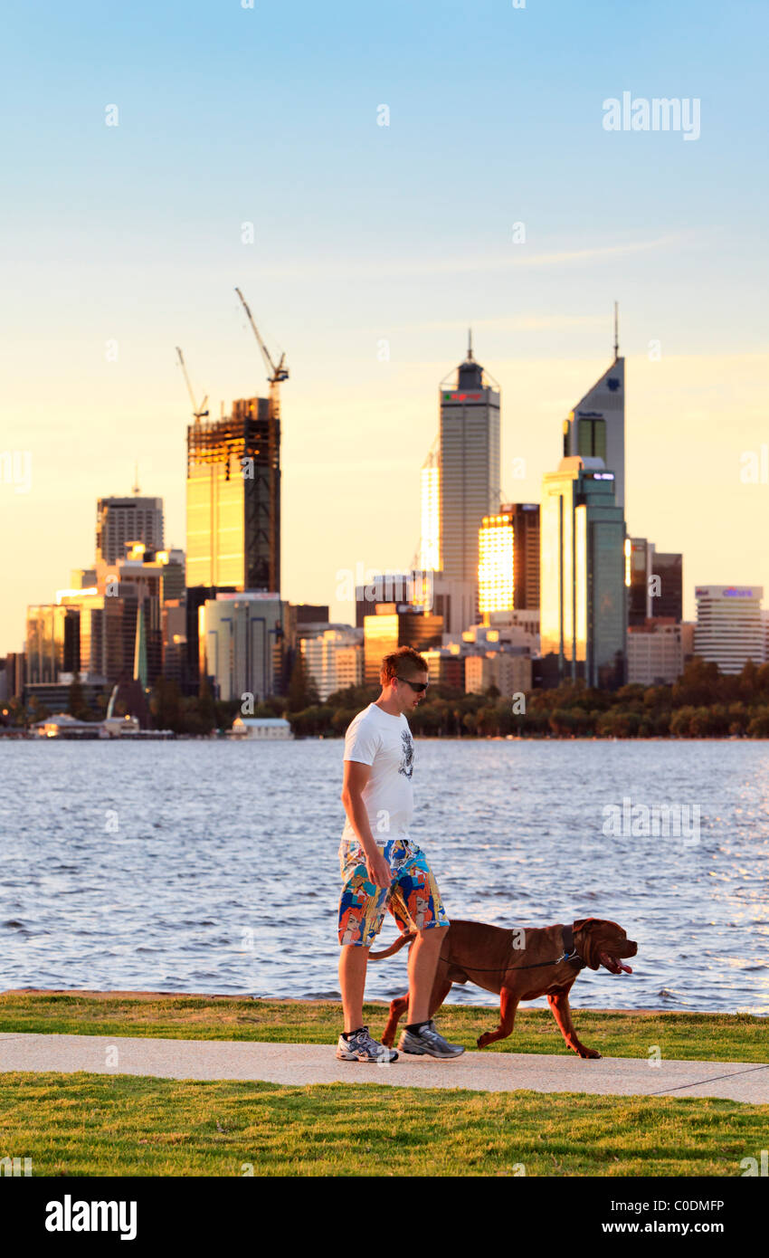 Man walking a dog down path beside river with city in the background. - Stock Image