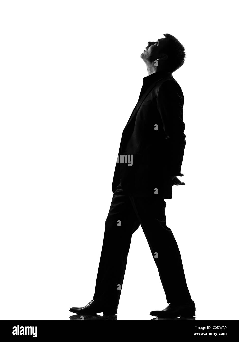 silhouette caucasian business man walking musing looking up expressing behavior full length on studio isolated white - Stock Image
