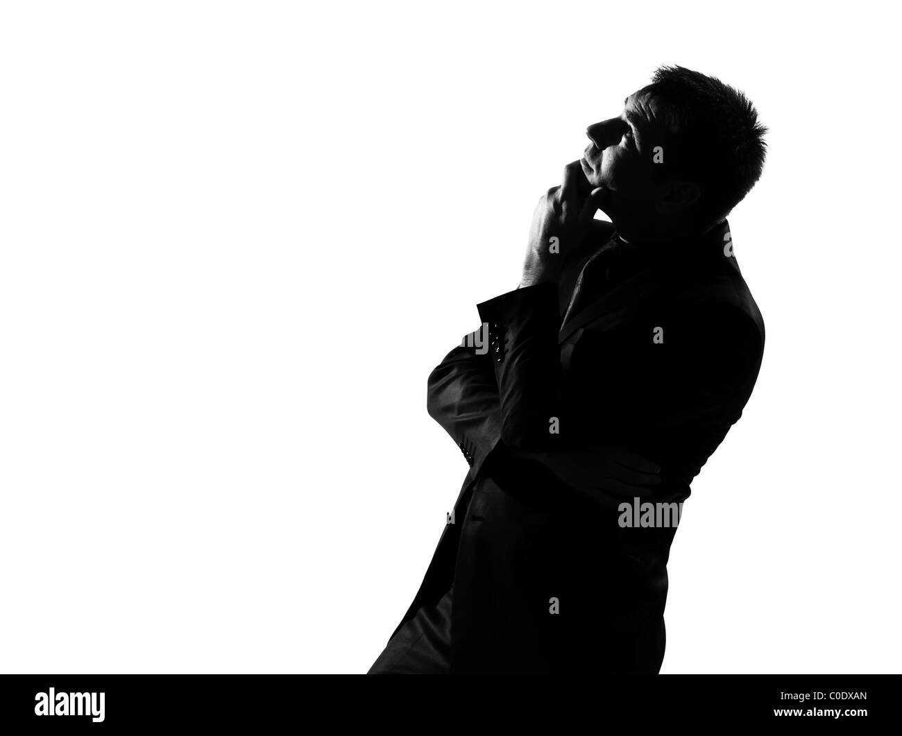 silhouette caucasian business man musing daydream looking up behavior full length on studio isolated white background - Stock Image