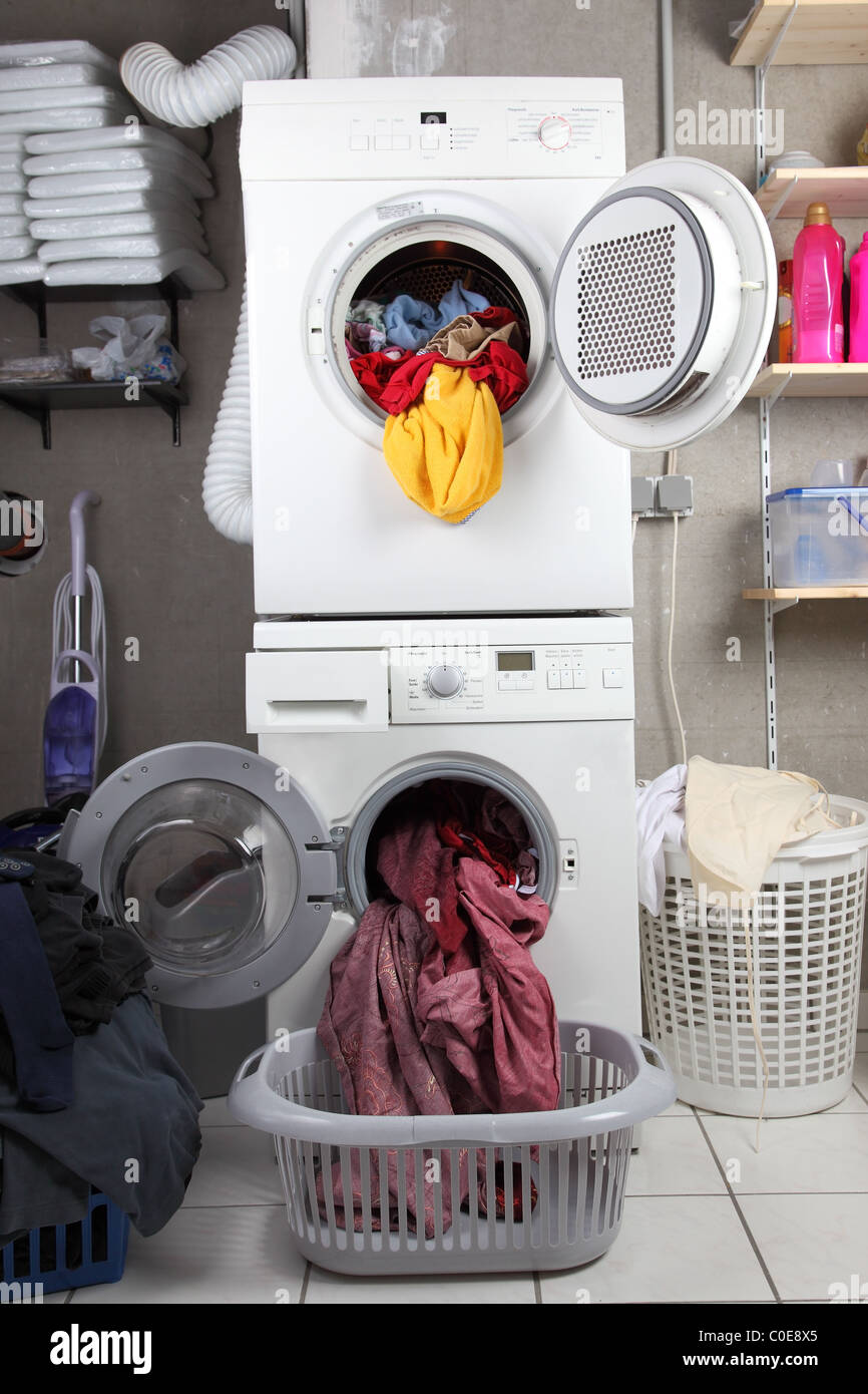 Baskets of dirty laundry in the washing room with dryer and washing machine - Stock Image