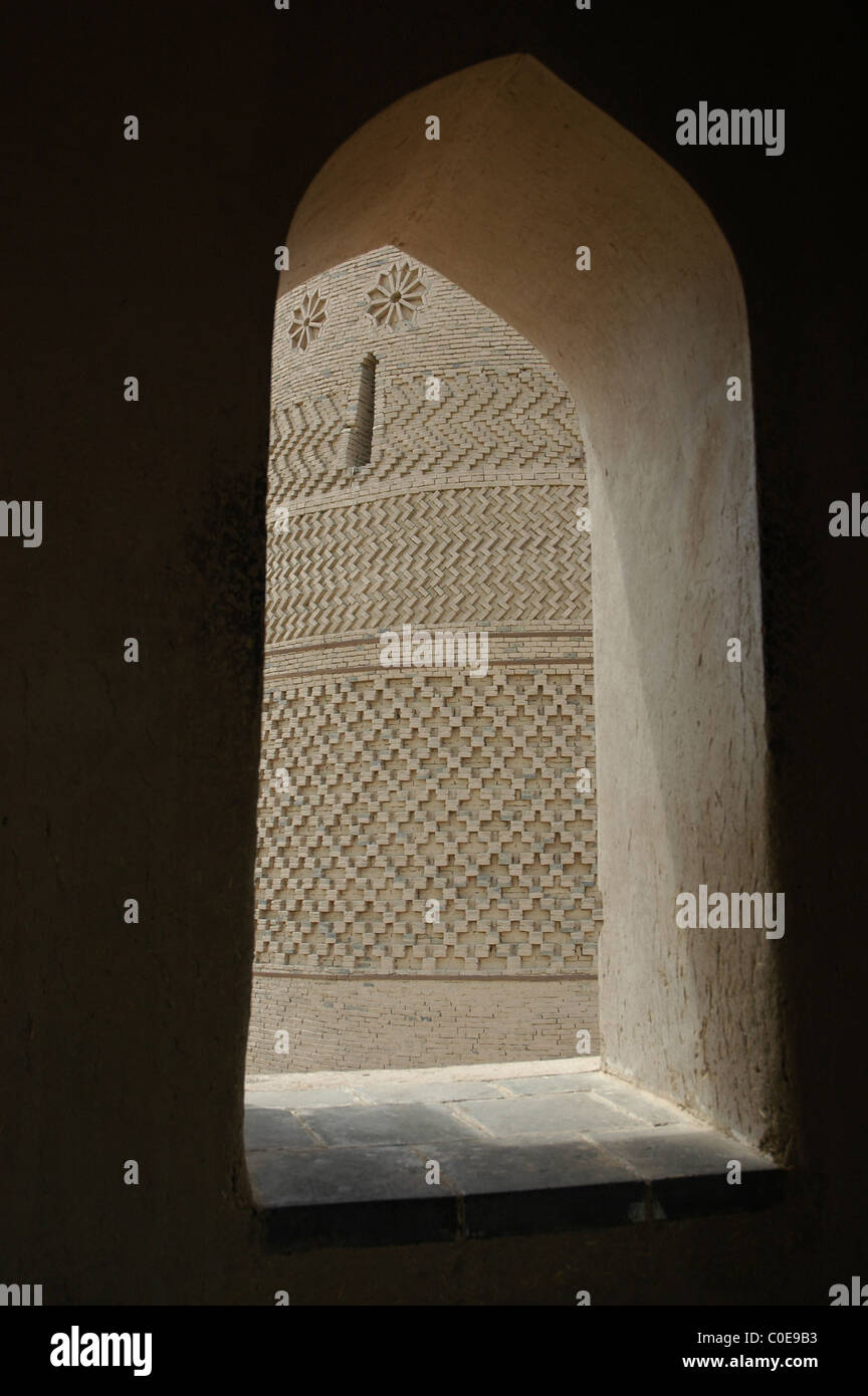View of intricate brickwork of Emin mosque, Turpan, through a stone window Stock Photo