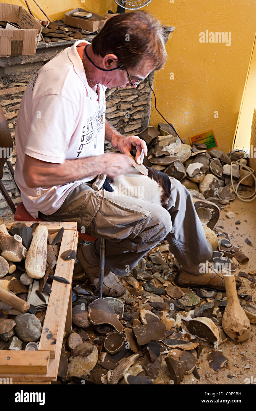 Artisan demonstrating prehistoric tools using flint to scrape a hide Les Eyzies Dordogne France French Europe - Stock Image