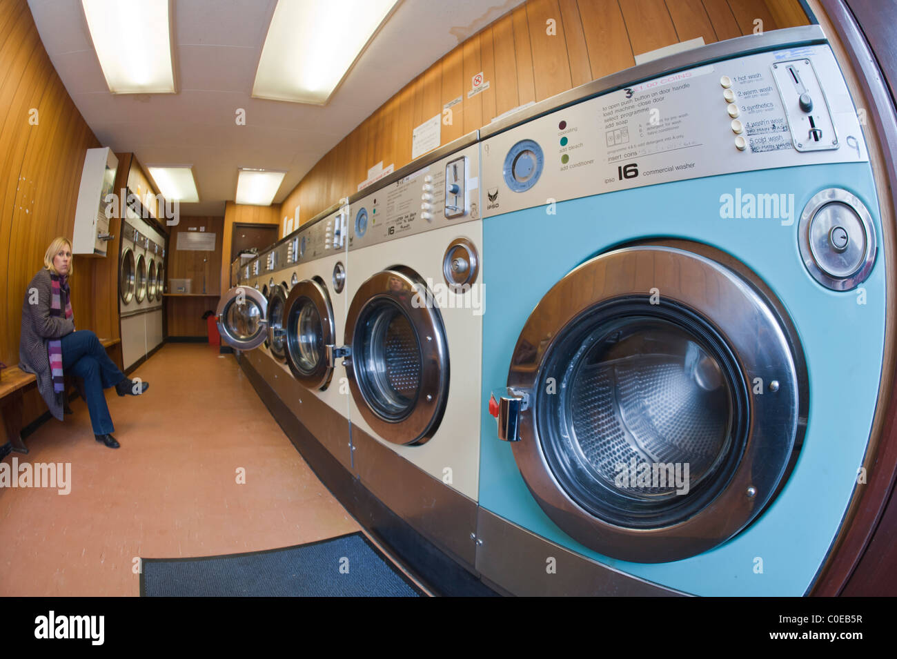 A laundrette with commercial washing machines and a MODEL RELEASED woman waiting for her washing in the background - Stock Image