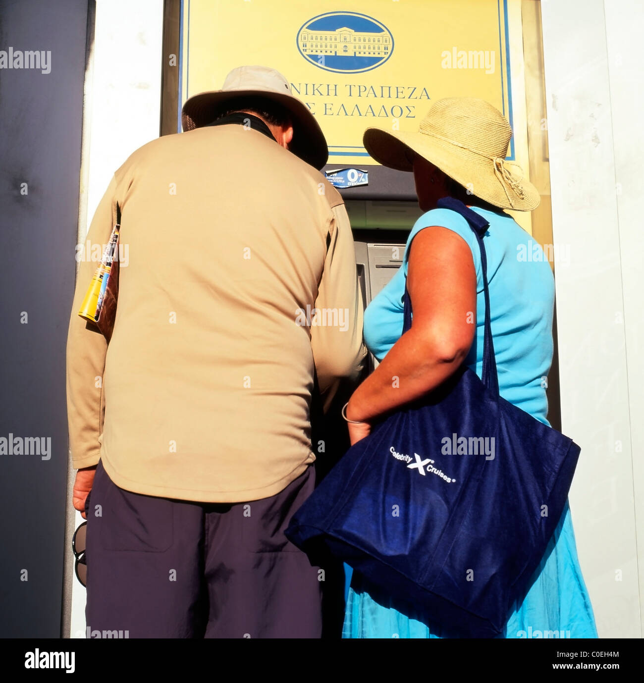 A middle-aged couple tourists getting money out from an ATM cash machine Santorini, Greek Islands, Greece  KATHY Stock Photo
