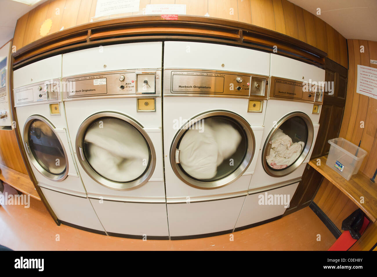 A laundrette with commercial driers showing movement as they spin in the Uk - Stock Image