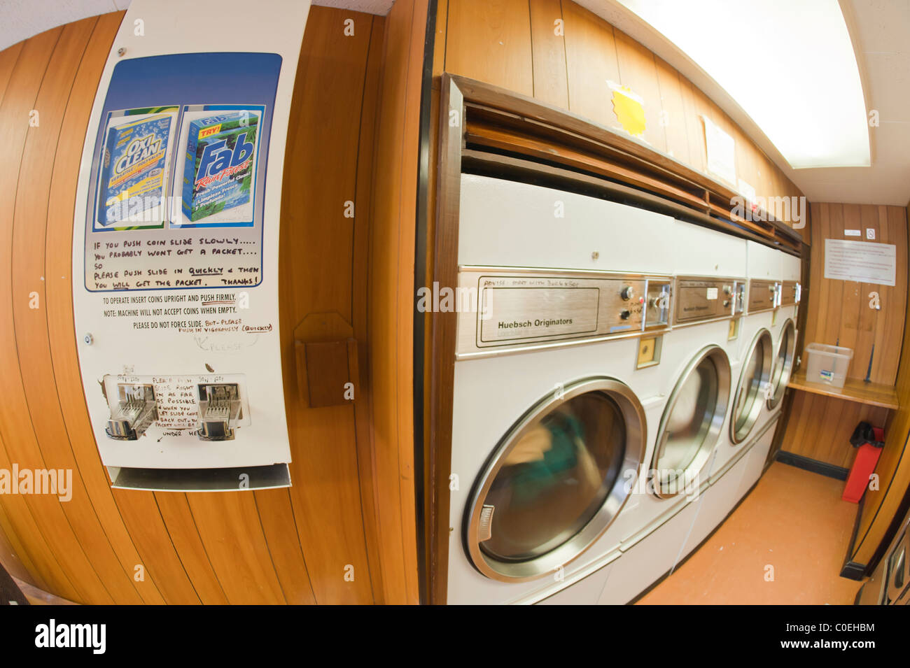 A washing powder vending machine in a laundrette with commercial driers showing movement as they spin in the background - Stock Image