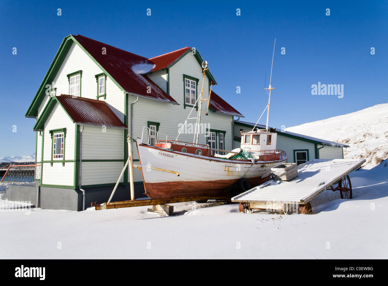 A boat and a floating pier wait behind the Western Emigration Center in Hofsos, Iceland. - Stock Image