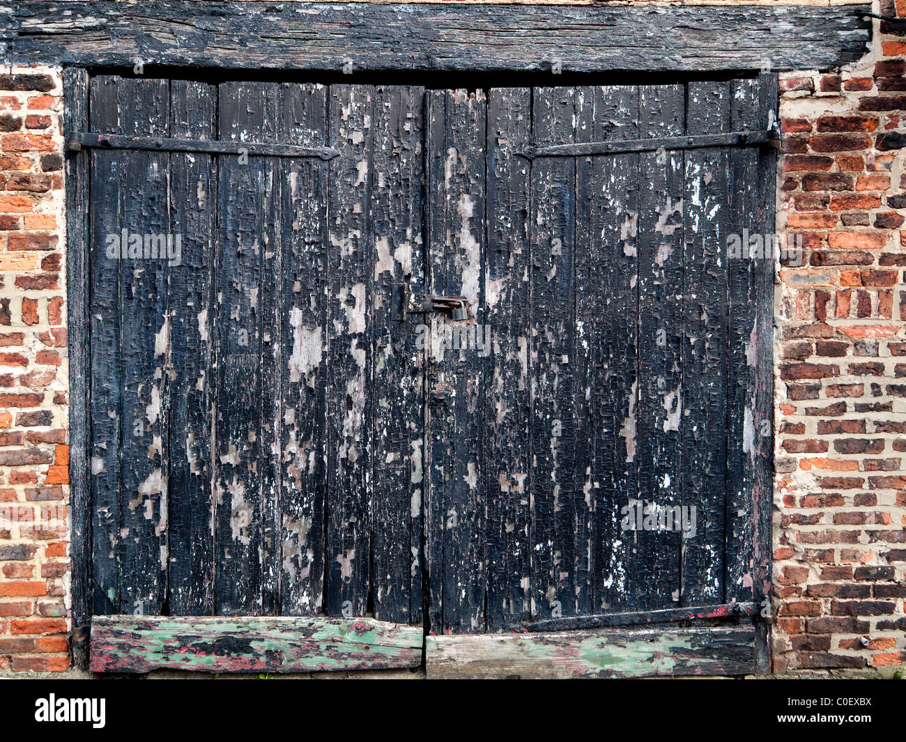 Old wooden garage door in need of redecoration with black paint