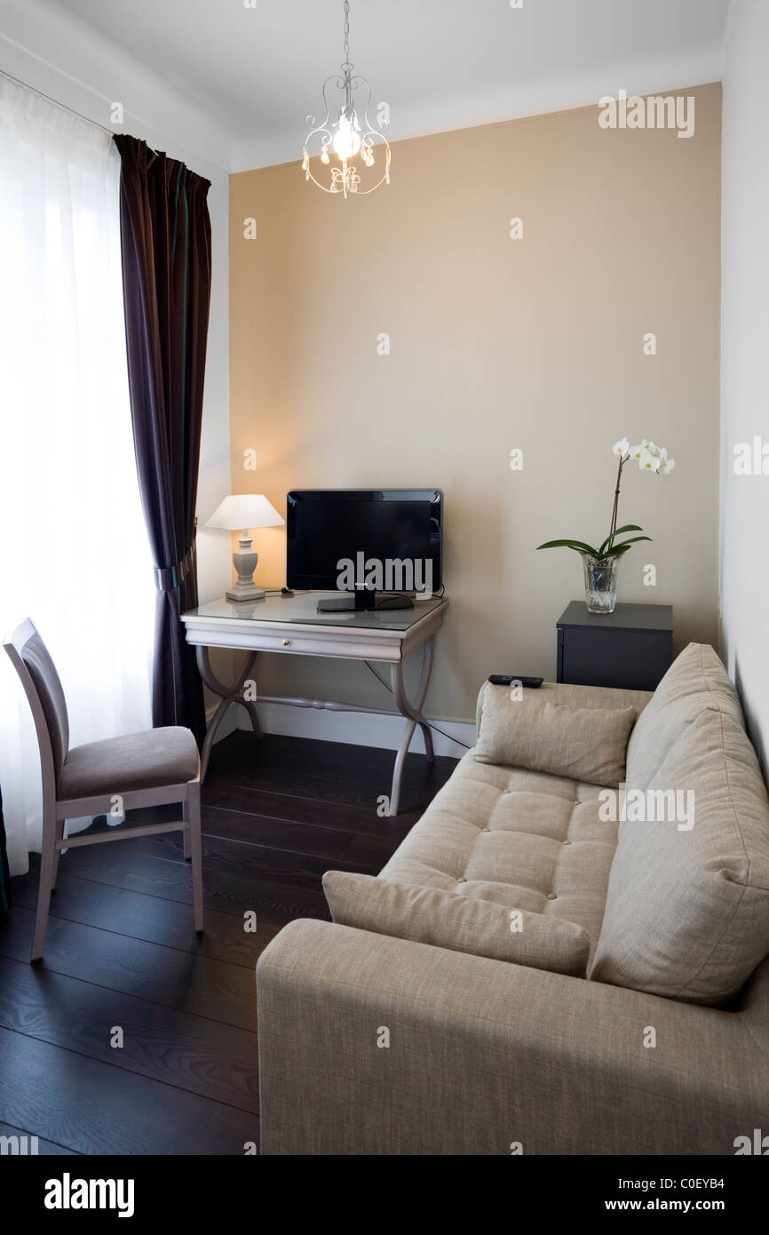 A small private lounge with television set in a suite (France).  Petit salon avec télévision dans une - Stock Image