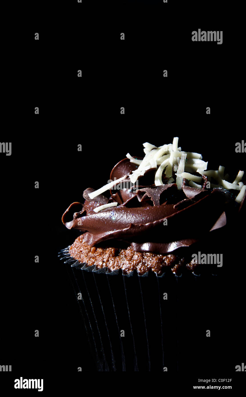 Single chocolate cup cake on a black background - Stock Image