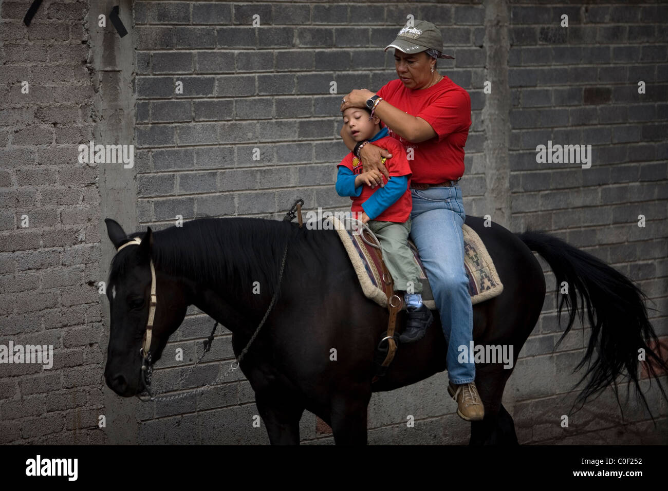 Equine Therapist Guadalupe Pena treats a boy who has infantile cerebral paralysis during his horse therapy session - Stock Image