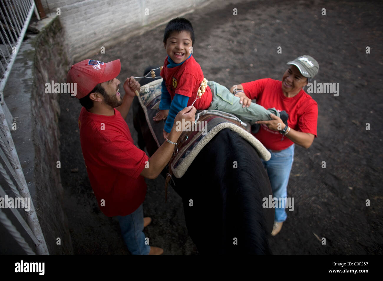 Equine therapists treat a boy who has infantile cerebral paralysis during his horse therapy session in Mexico City - Stock Image
