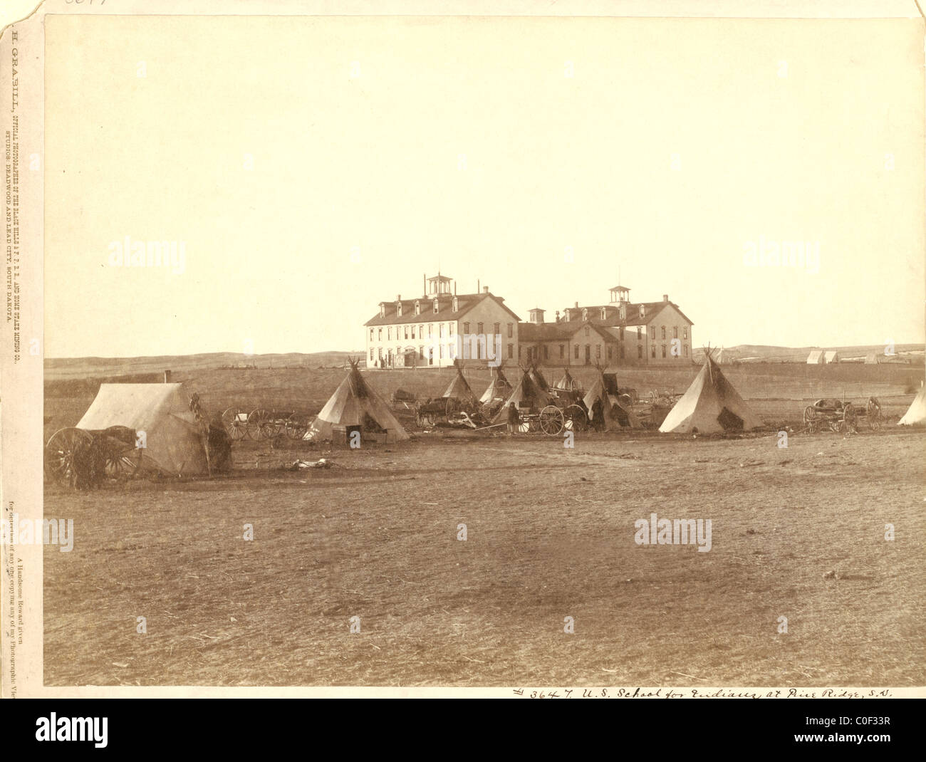 U.S. School for Indians at Pine Ridge, South Dakota with  Small Oglala tipi camp in front 1891 Stock Photo