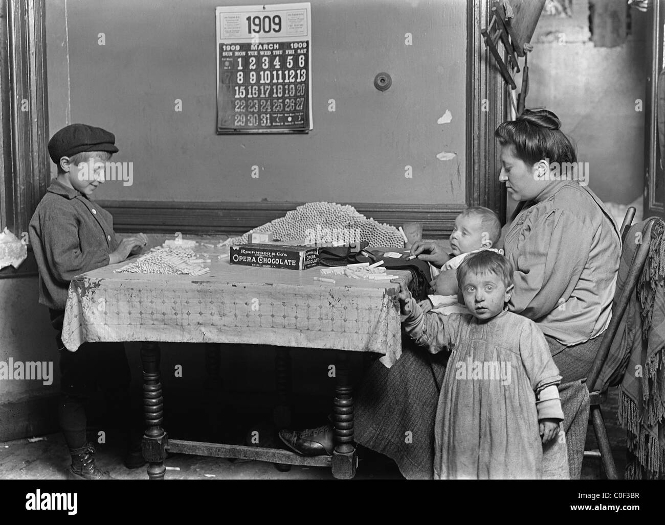 Widow & boy rolling papers for cigarettes in a dirty tenement. Location New York City 1908 - Stock Image