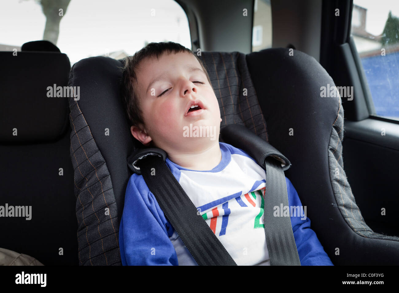 young child alone in the back seat of a car - Stock Image