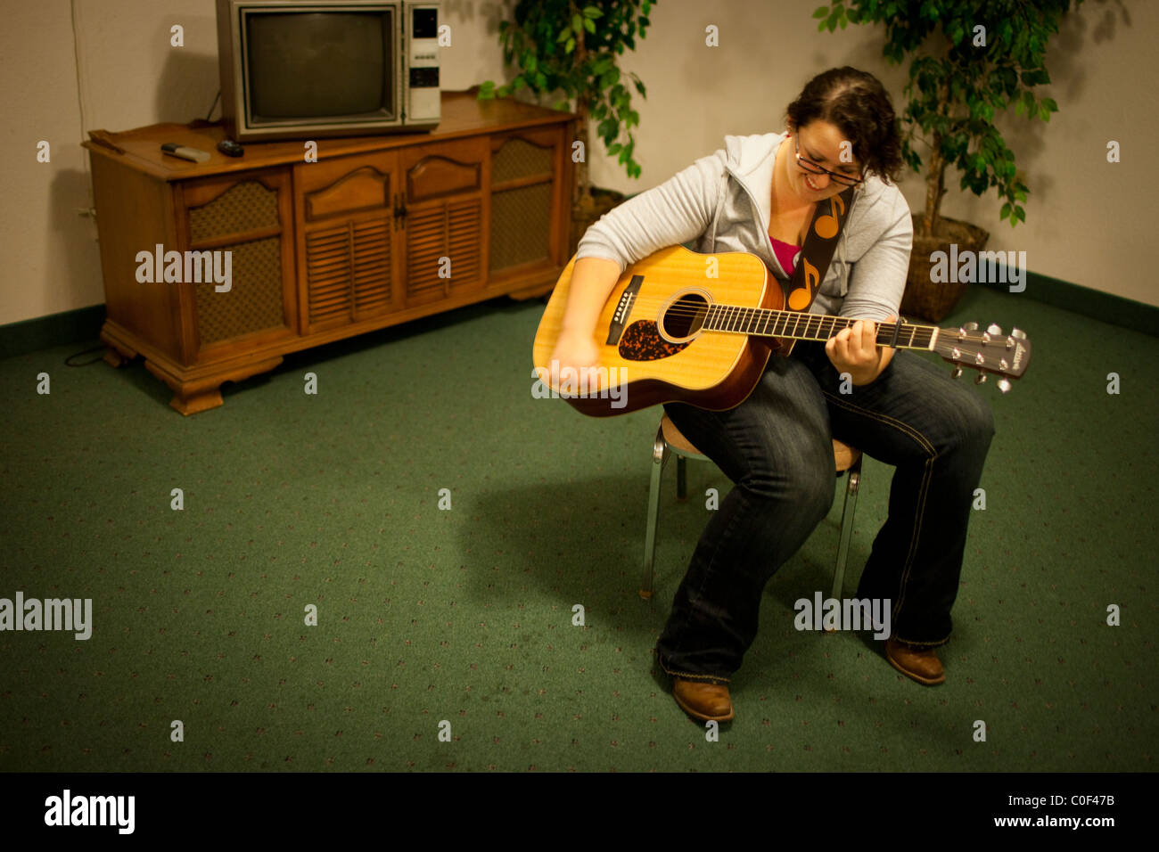 Fresno, California, United States. An obese teen plays her guitar ...