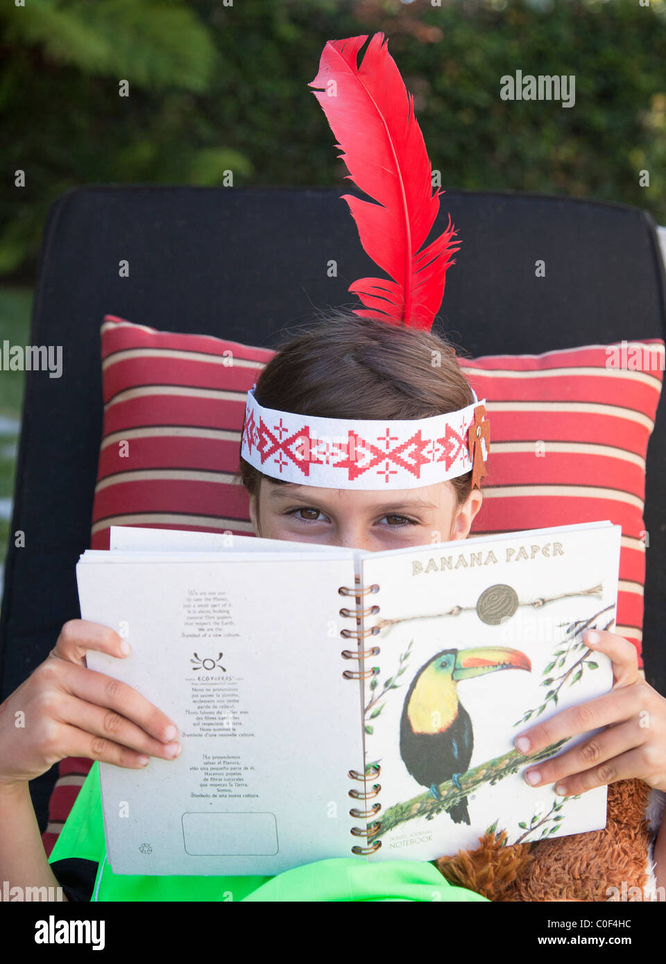 Girl wearing indian feather peeking over book - Stock Image