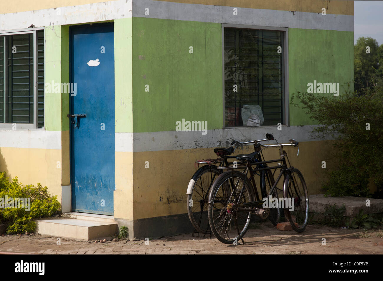 Two old-fashioned bicycles leant against a wall outside a small outbuilding at a service station in Bangladesh - Stock Image