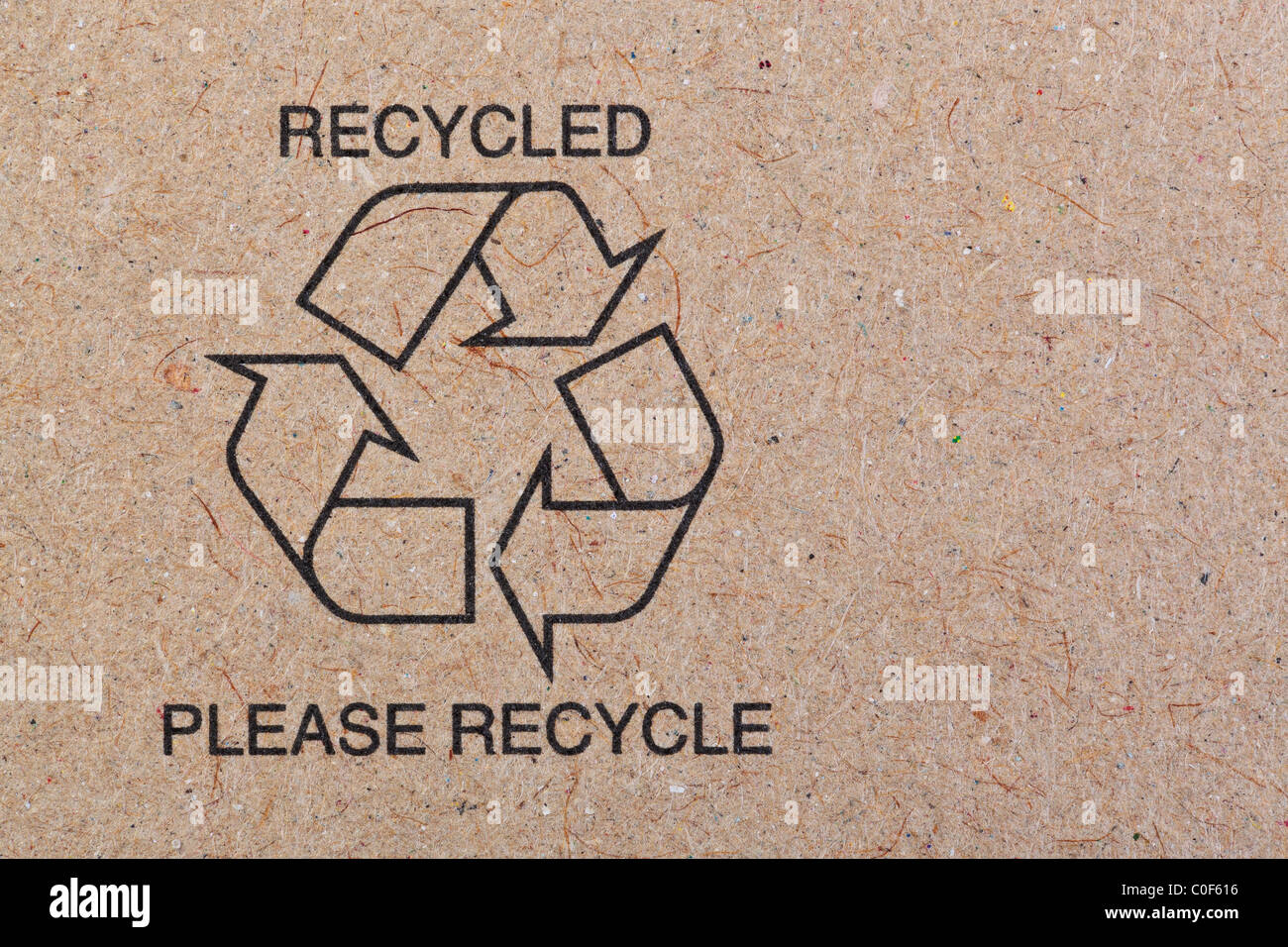 Close up photo of the recycle symbol printed on a recycled cardboard background. - Stock Image