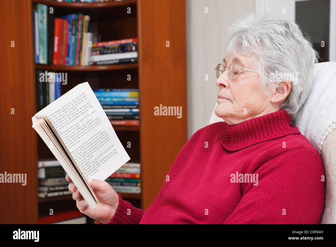 Someone elderly woman wearing a red jumper relaxing sat reading a paperback book in a living room with a bookcase - Stock Image