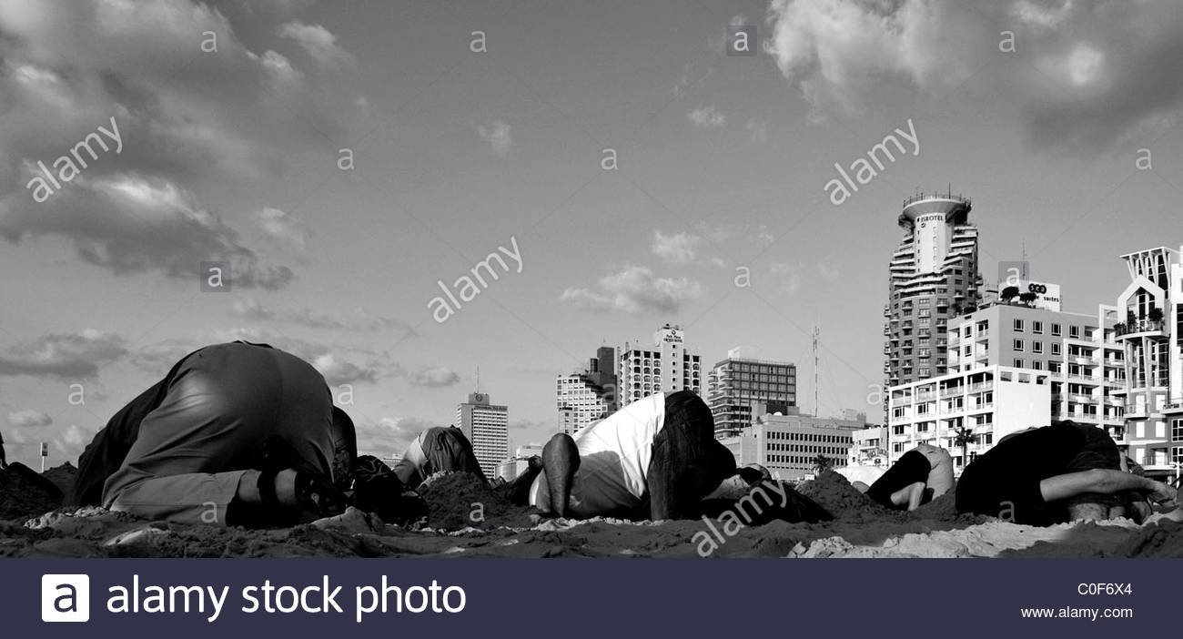 Young people burying their head in the sand during humorous event in Jerusalem Beach in Tel Aviv Israel - Stock Image