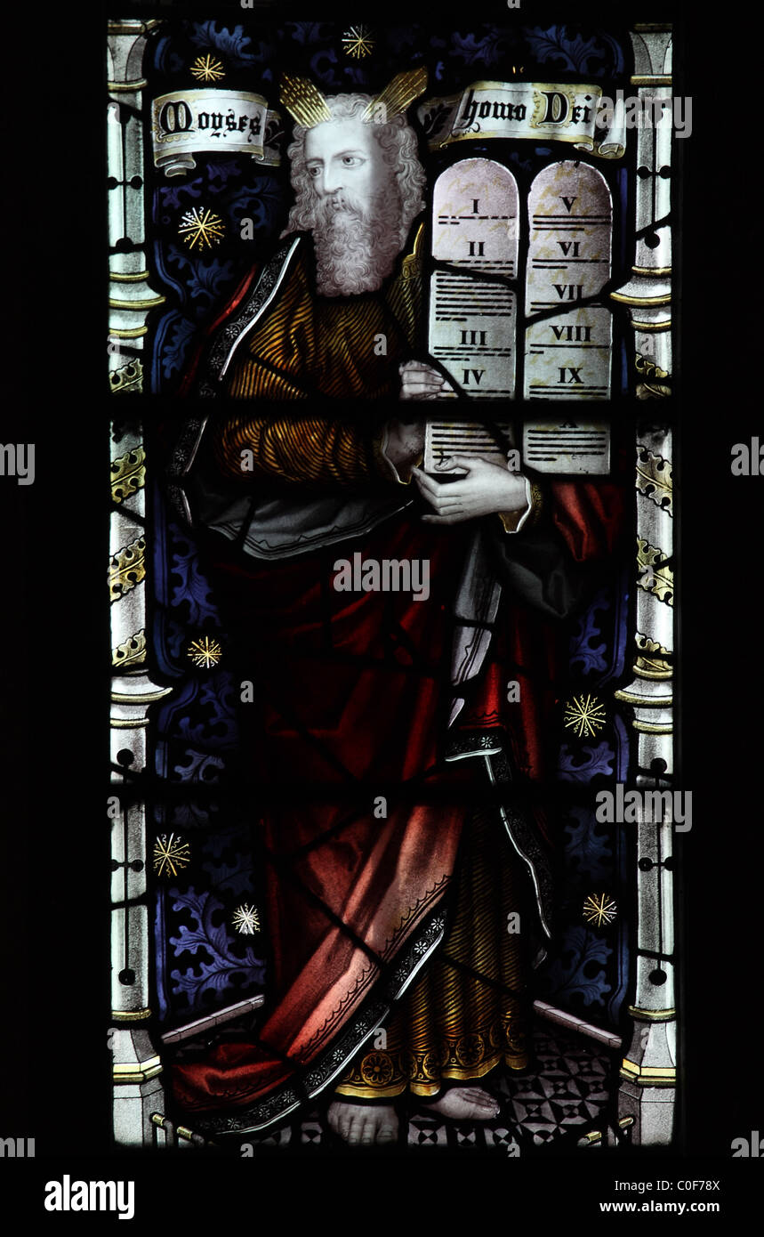 A stained glass window by C E Kempe & Co. depicting Moses with the Commandment Tablets - Stock Image