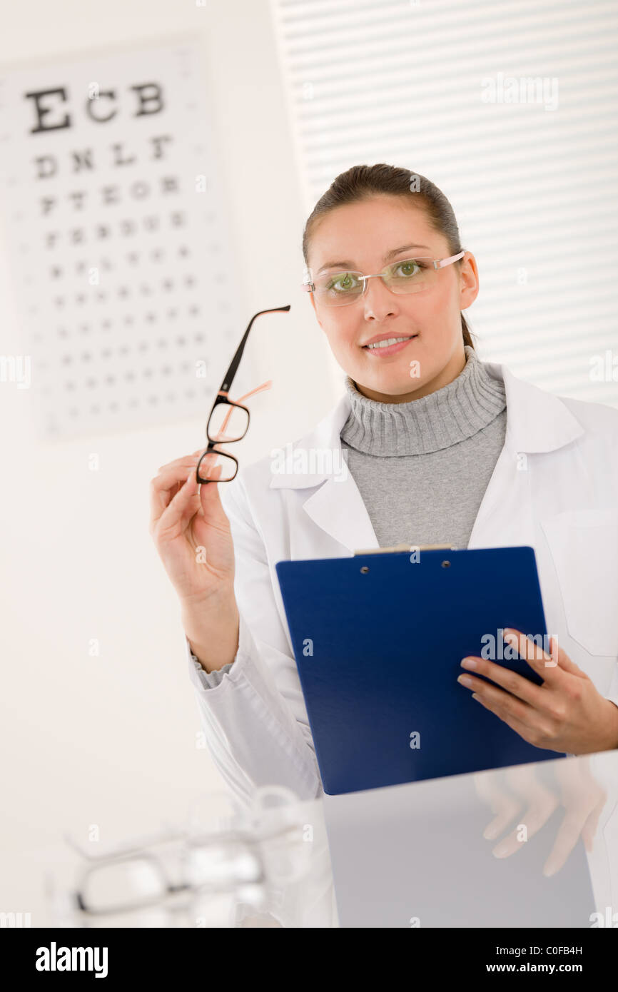Optician doctor woman with prescription glasses and eye chart - Stock Image