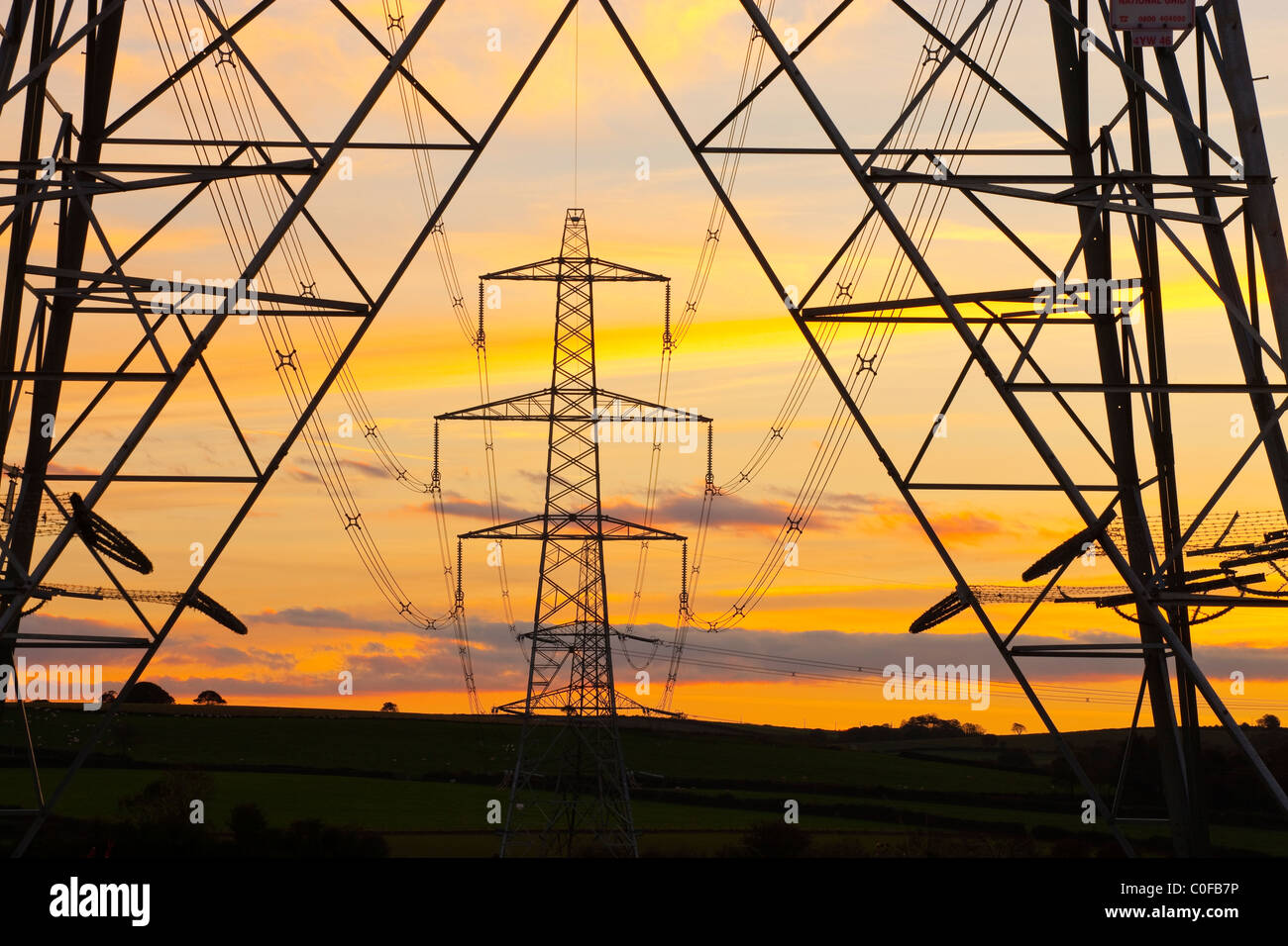 An electricity pylon of the National Grid in Wales at sunset - Stock Image