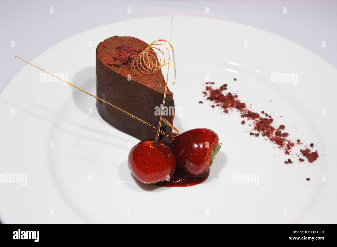 Chocolate mousse with two strawberries gourmet dessert course on a white plate from above - Stock Image