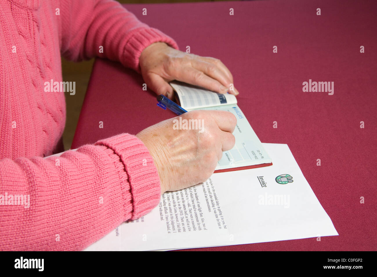 Close up pensioner writing cheque to pay an invoice Stock Photo