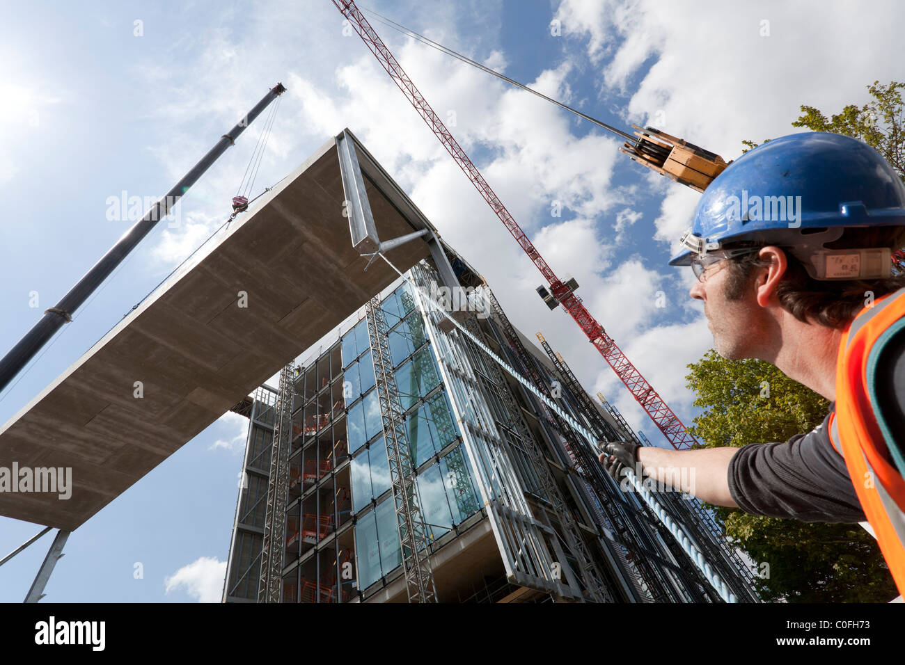 Operator holding ropes to guide crane lift on construction site. - Stock Image
