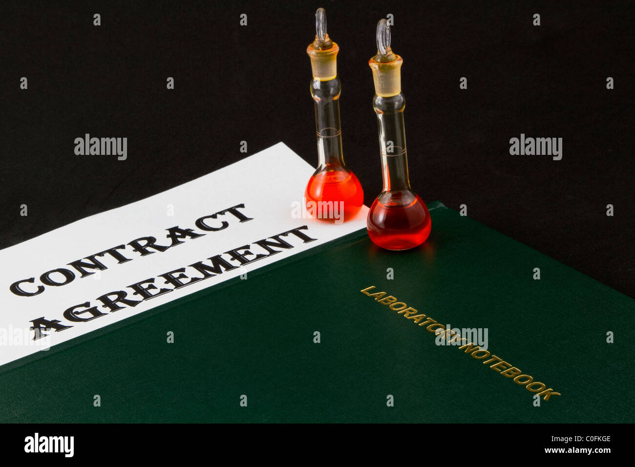 Contract Agreement with two beakers and a laboratory notebook reflects scientific big business efforts. - Stock Image
