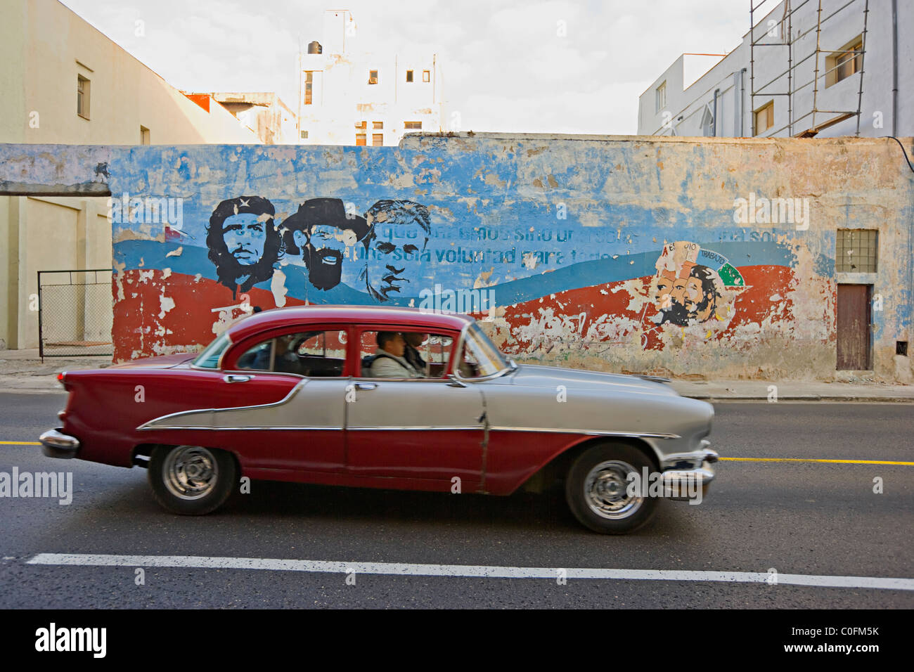 An old American 1950s automobile driving past a painted mural of Che Guevara in Havana  Cuba Stock Photo