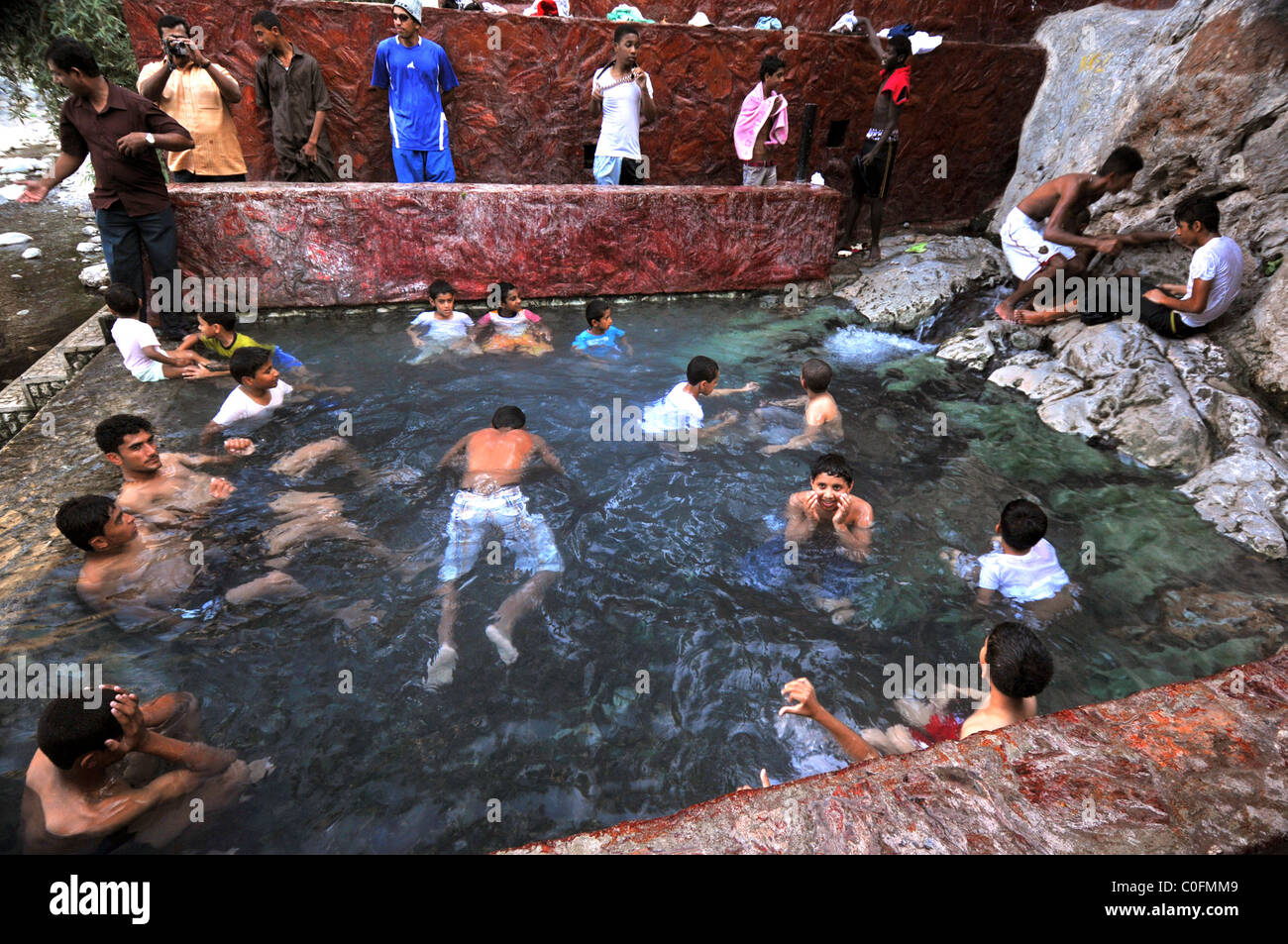 Youths bathing in the hot spring water at Nakhal. The Sultanate of Oman. - Stock Image