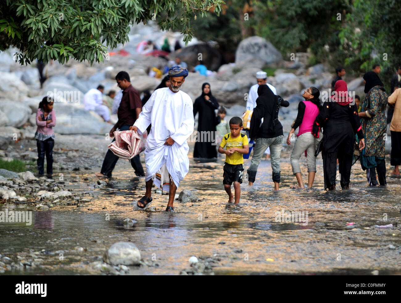 Families paddling in the hot spring water at Nakhal. The Sultanate of Oman. - Stock Image