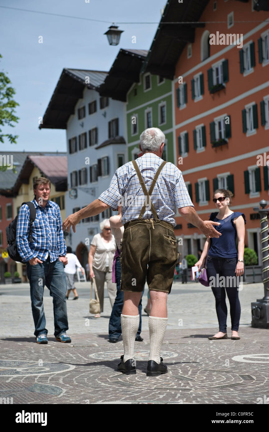 A guided walking tour of Kitzbuhel with the male guide wearing lederhosen breeches Tyrol. Austria. - Stock Image