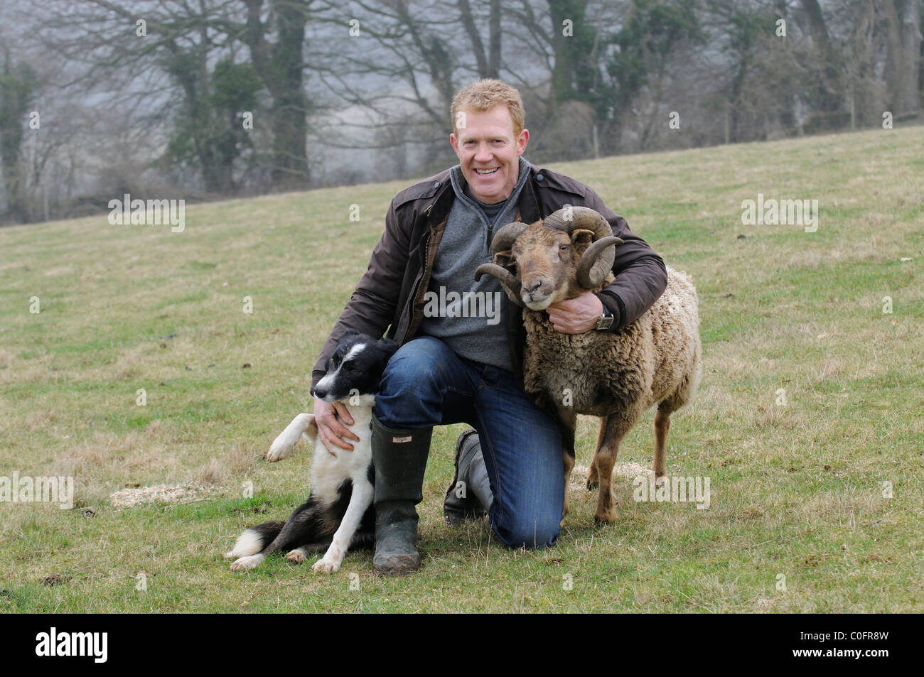 Adam Henson Cotswold farmer with his dog and a rare breeds Soay Ram on Adam's farm. BBC Countryfile tv presenter - Stock Image
