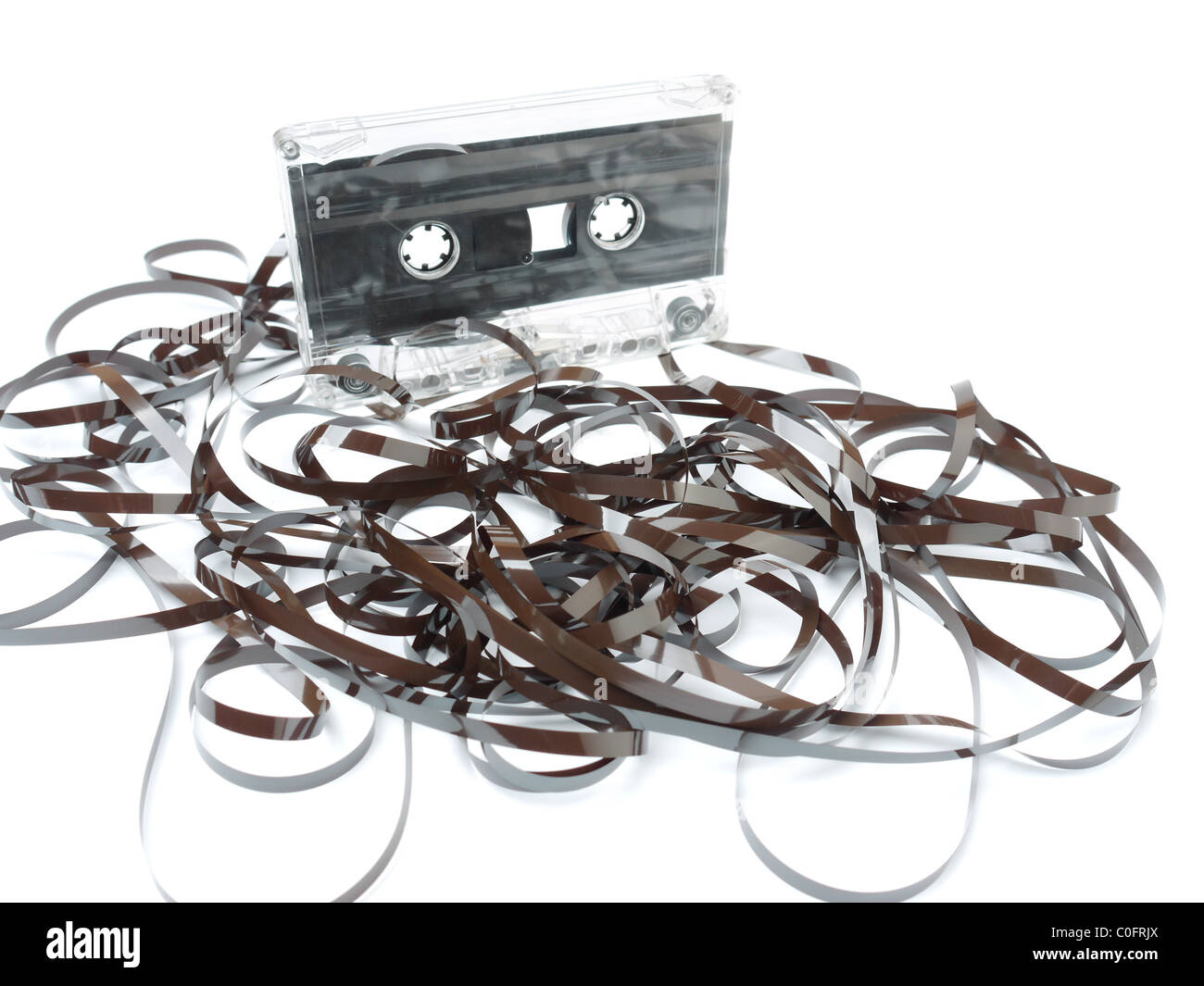 Old audio cassette tape pulled out and tangled on white background - Stock Image