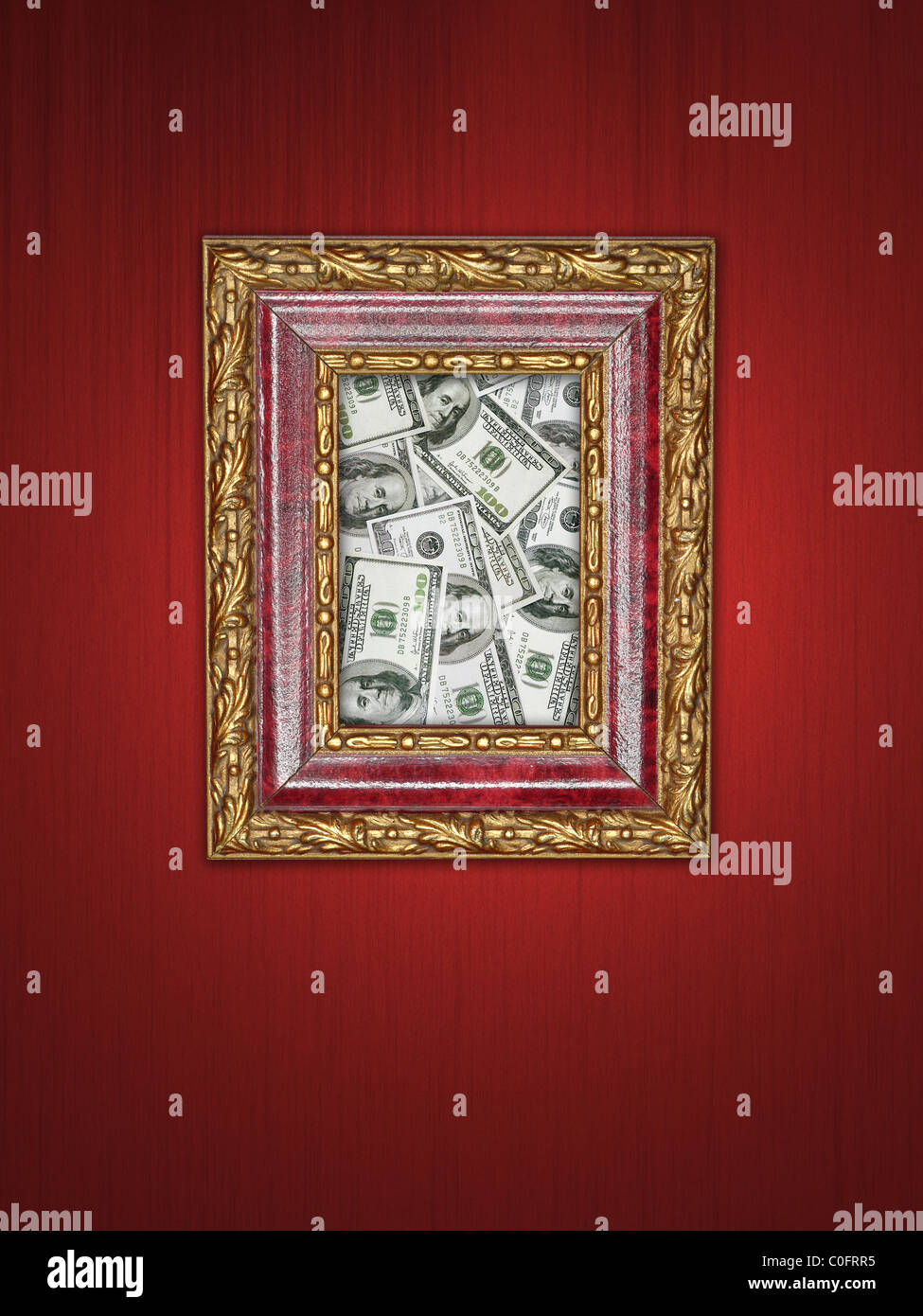 Pile of one hundred dollar banknotes in wooden picture frame with golden ornaments hanging on purple wall - Stock Image