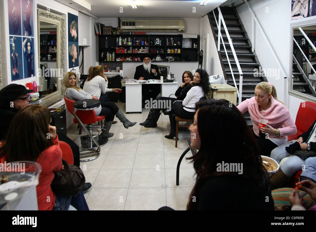 An Orthodox Jewish man giving religious lecture to young women in a beauty parlour in Tel Aviv Israel - Stock Image