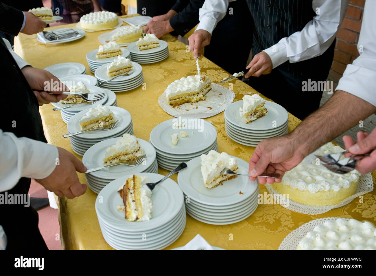waiters serving wedding cake - Stock Image