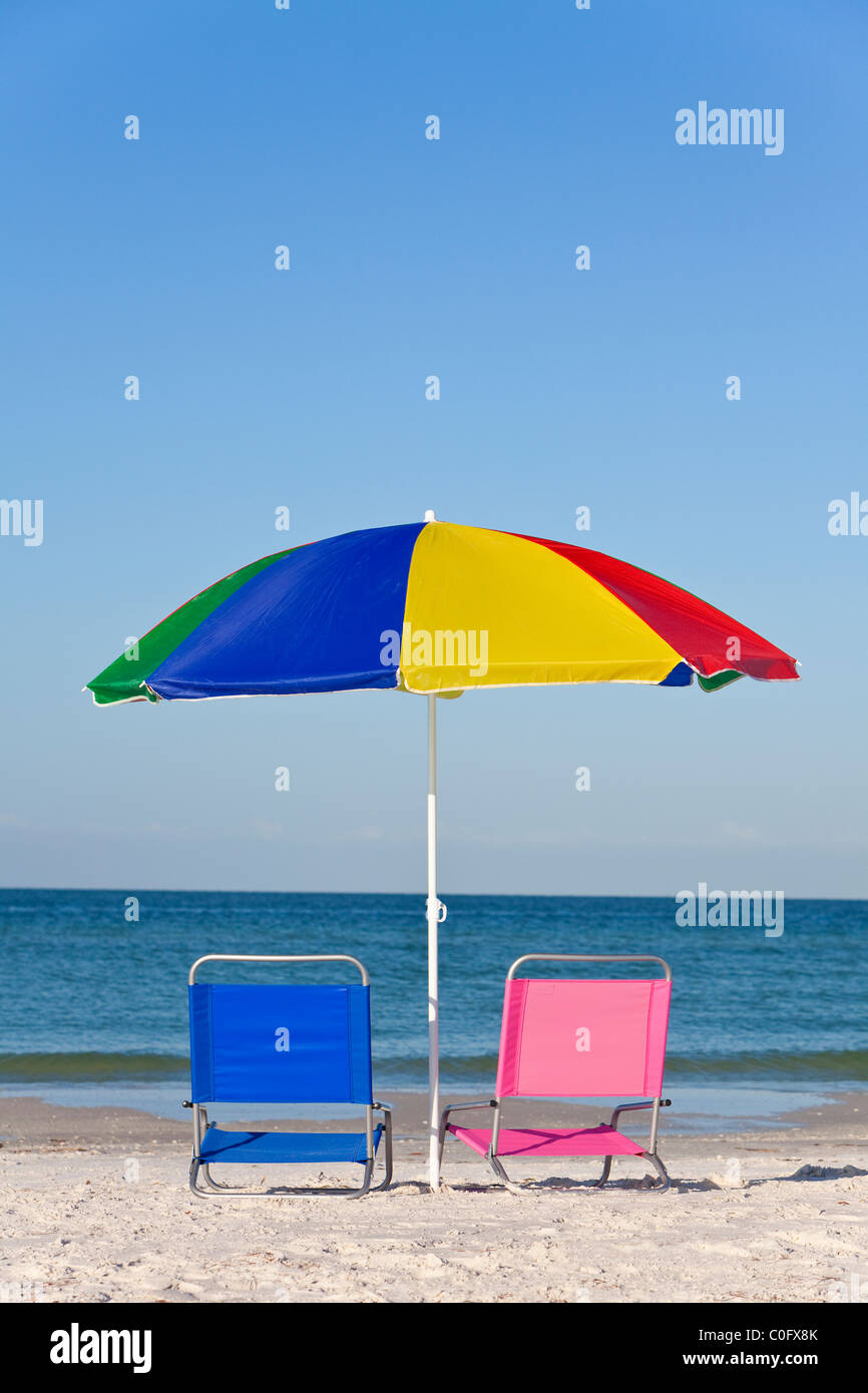 Pink and blue deck chairs on a beach underneath a colorful umbrella or parasol - Stock Image