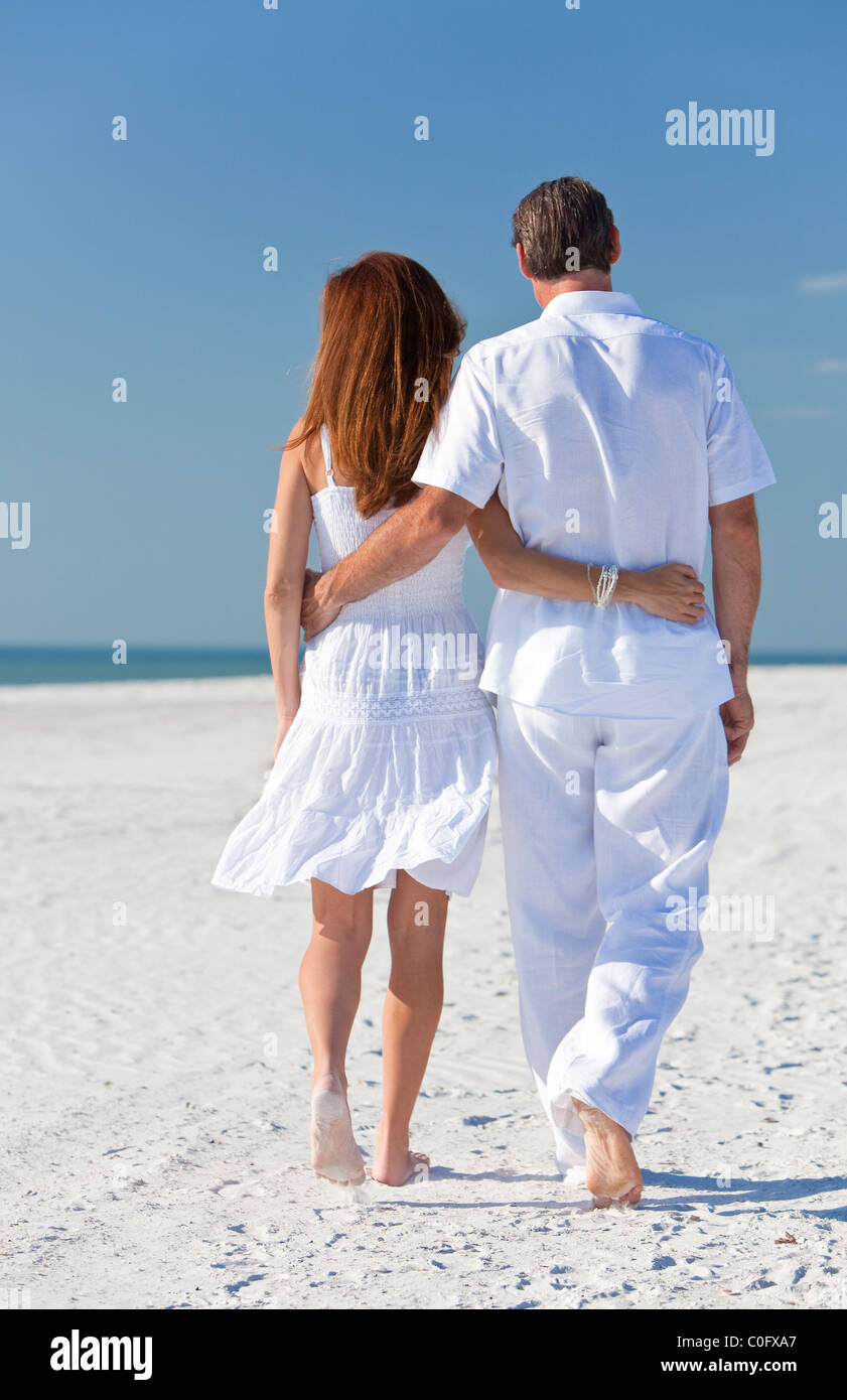 ff3aaa8f3b5c Rear view of man and woman romantic couple in white clothes walking on a deserted  tropical beach with bright clear blue sky
