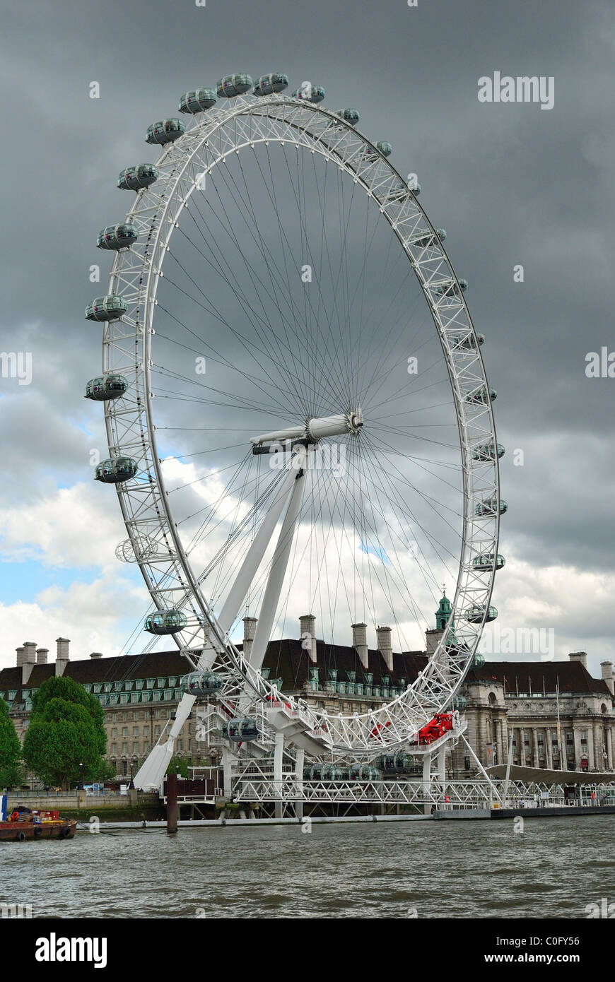 London Eye from the Thames set against a stormy dark sky - Stock Image