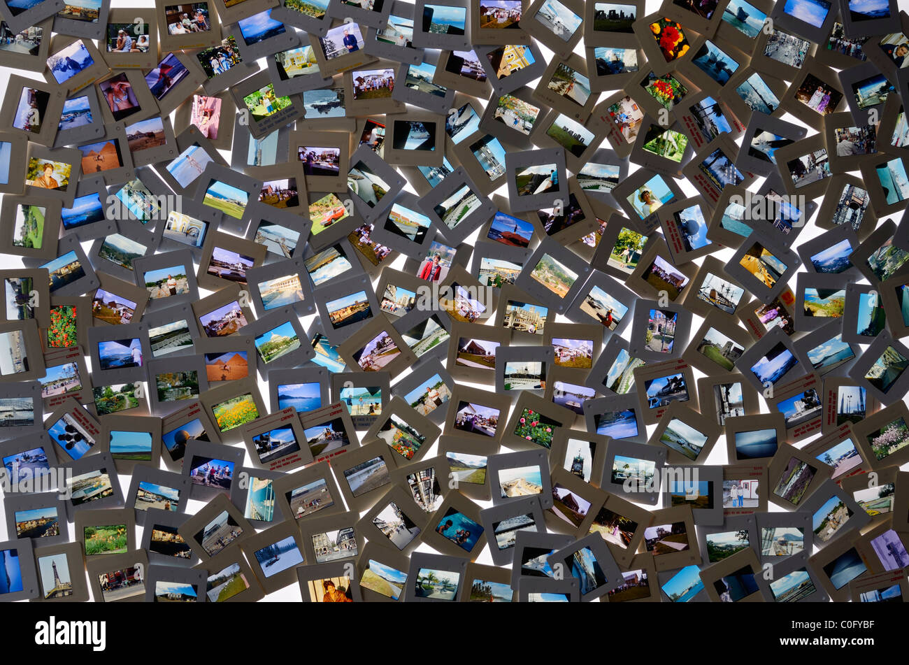 Large collection of color film slide snapshot pictures of past vacations on a light table - Stock Image