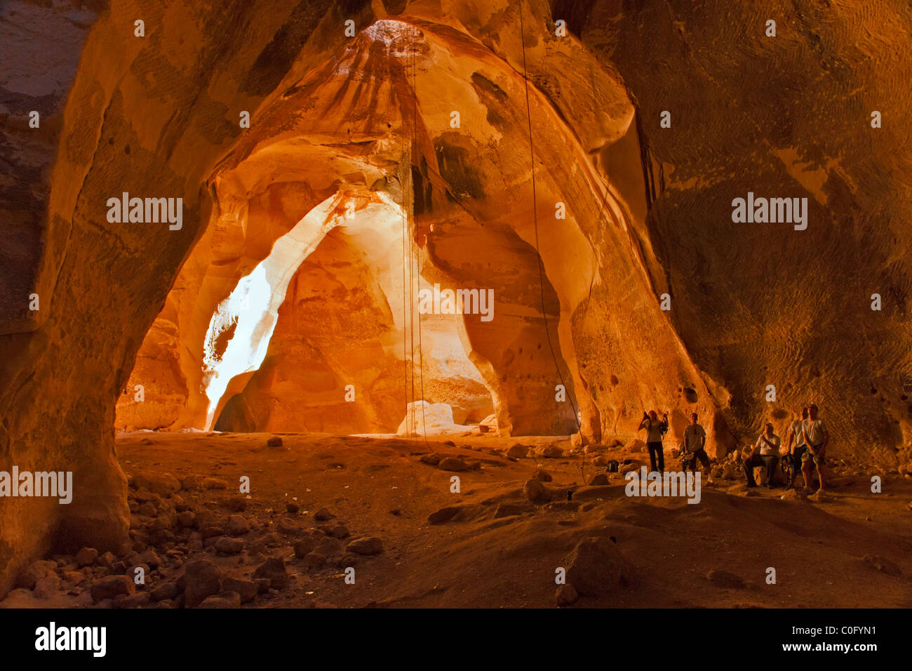 People wait for a group member to rappel from the top of the Bell caves near Luzit, Israel. - Stock Image