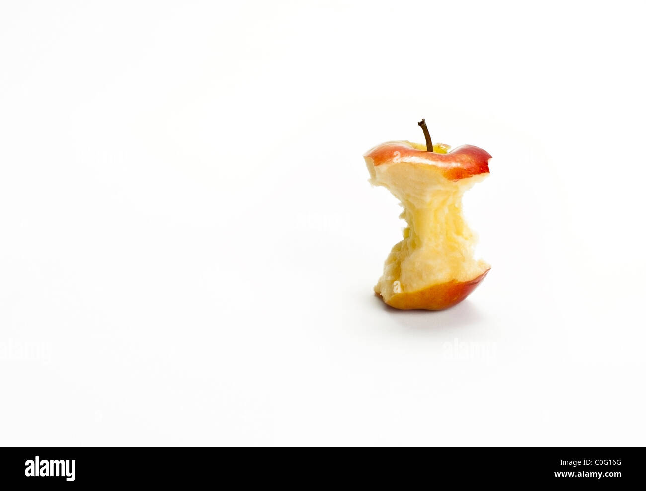 An apple core composed off center with white background and room for copy or cutout. - Stock Image